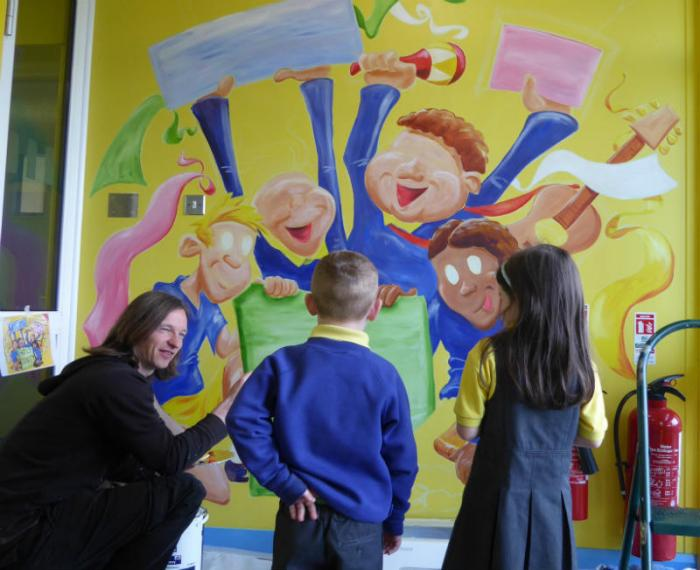 Kevin talks to pupils while painting the mural at Mill Street