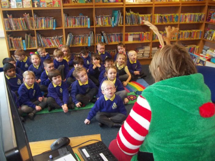 Mrs McElroy's P1 class enjoy Christmas stories in the Library with Marion