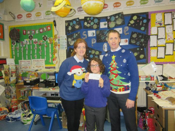 Mrs Cathcart and Mr Treacy present a cheque for £200 to Samuel from P6. Samuel is raising money for Cancer Research.