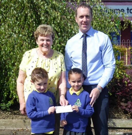 Myrtle Hemphill from Parkinson Support Fermanagh receives a cheque from Holy Trinity Primary & Nursery School.