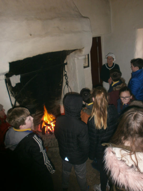 P7 enjoy the warm fire in a cottage during their visit to the Ulster American Folk Park