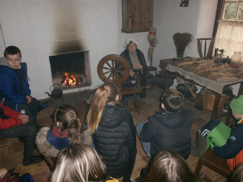 P7 enjoy the warm fire while listening to stories from the new world during their visit to the Ulster American Folk Park